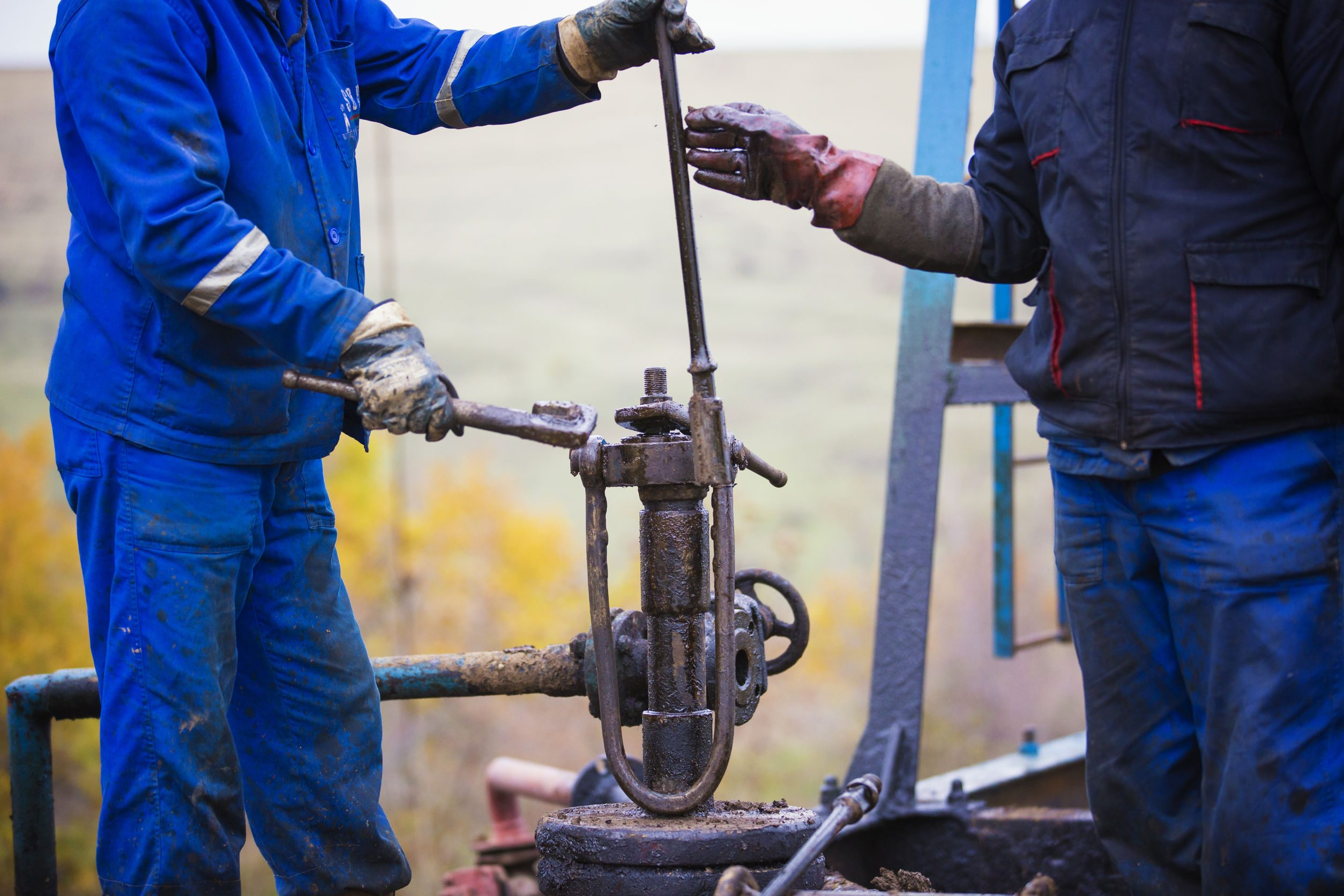 oil workers check oil pump